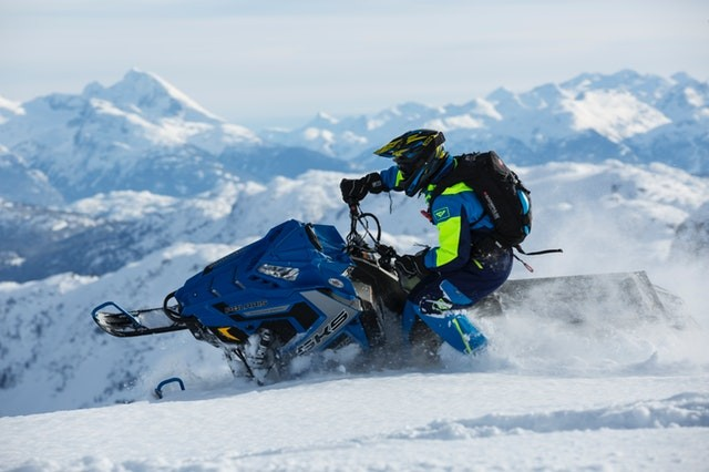 picture of man in blue and green long sleeved suit riding on snowmobile
